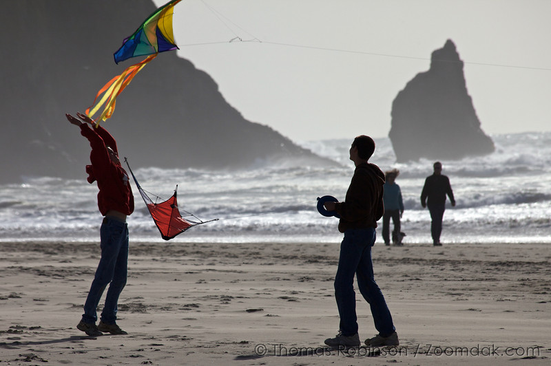 Kids launch a colorful kite into the air along the shore in Cannon Beach.