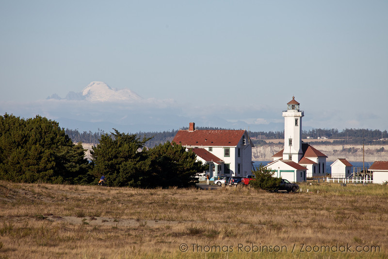 Mt. Baker peaks out of the clouds behind Point Wilson Lighthouse in Port Townsend.