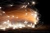 Wind blows sparks from a TNT glittering fountain firework sideways across the beach in Gearhart, Oregon.