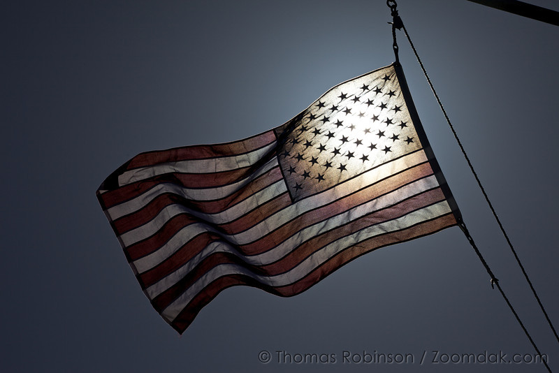 The American flag flaps in the wind illuminated by the sun.