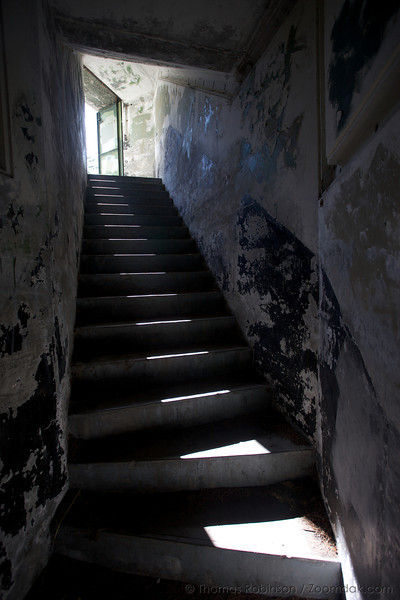 "A staircase leads up into the light of the doorway above. <br /> <br /> ""Fort Worden, along with the heavy batteries of Fort Flagler and Fort Casey, once guarded nautical entrance to Puget Sound. These posts, established in the late 1890s, became the first line of a fortification system designed to prevent a hostile fleet from reaching such targets as the Bremerton Naval Yard and the cities of Seattle, Tacoma and Everett. Construction began in 1897 and continued in one form or another until the fort was closed in 1953. The property was purchased as a state park in 1955. Fort Worden is named after Rear Admiral John L. Worden.""<br /> - <a href=""http://www.parks.wa.gov/fortworden/history.aspx"">http://www.parks.wa.gov/fortworden/history.aspx</a>"