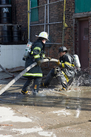 Explosion and fire with toxic smoke on Chicago's West Side, 3/10/06<br /> Squad 1fireman Kelly Burns making a splash.