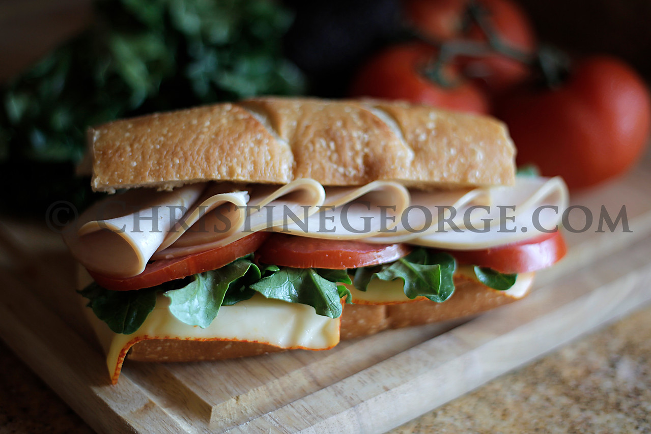 APPLE_SMOKED_TURKEY_SLICED_ON_FRENCH_ROLL_CUTTING_BOARD_VEGIES_CAG6560