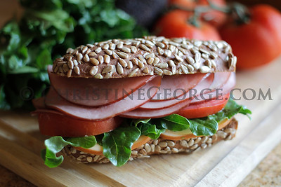UNCURED_BLACK_FOREST_BRAND_HAM_ON_WWHEAT_ROLL_CUTTING_BOARD_VEGIES__CAG6535