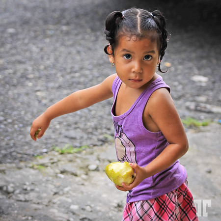 Pretty in purple for the purple day  * Obviously she didn't like the skin of the pear, because she was throwing it away, in the street :)  - Bocas Del Toro, Panama