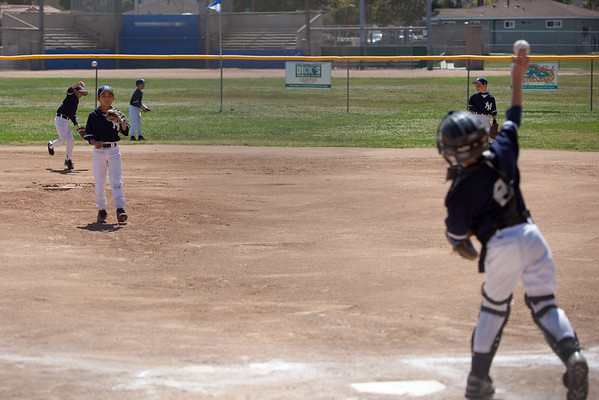 The catcher throws the ball back to JJ during warmups