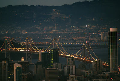 This photo was taken from the top of Twin Peaks in San Francisco in the early evening.  The skyline is along the eastern shore of SF, the two bridge segments make up the bridge running across the SF bay (via Treasure Island).  I believe the bulk of the buildings on the far shore are Berkeley, with the tower on campus centered in the shot.