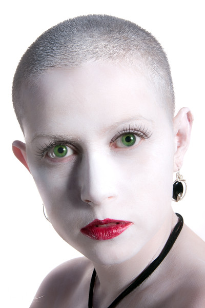 Bald model with white face and green eyes