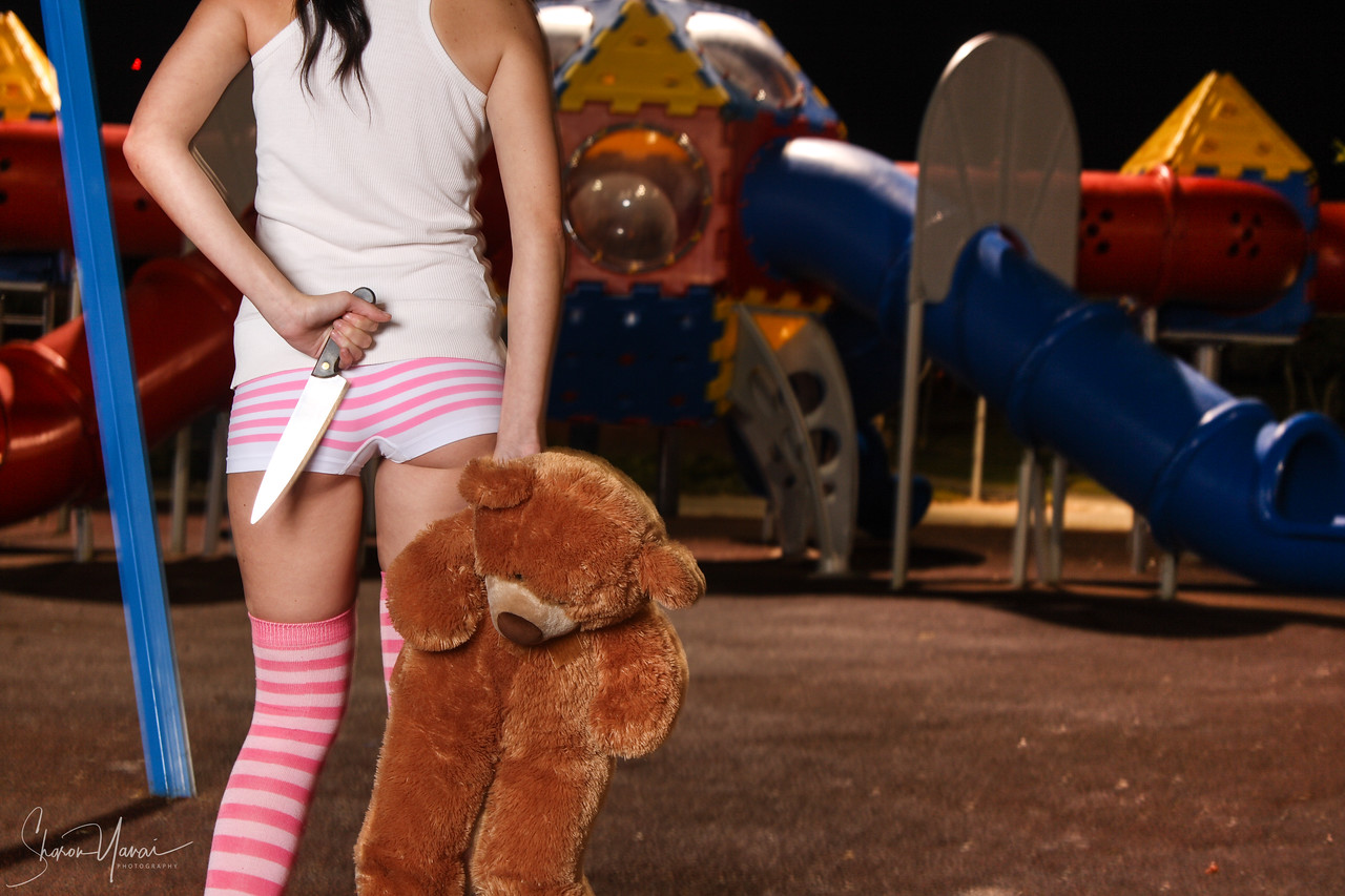 Girl holding a knife and a teddy bear on the playground at night