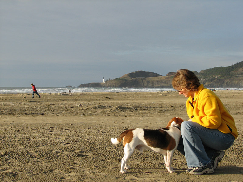 Pam & Tucker at the beach. You can see the Yaquina Head Lighthouse in the background.