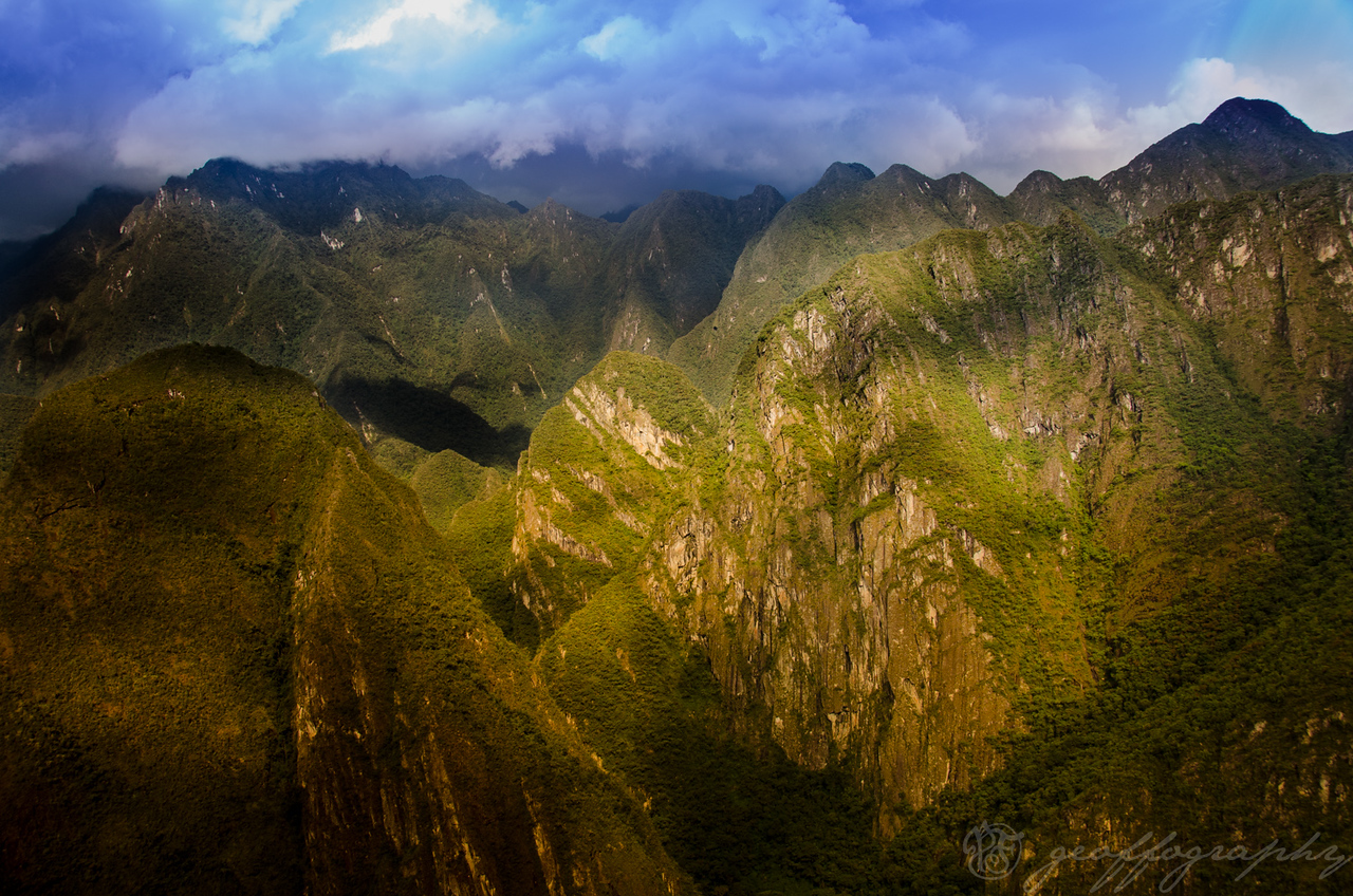 Passing Light: Sunlight passes through the clouds onto mountain ranges surrounding Macchu Picchu