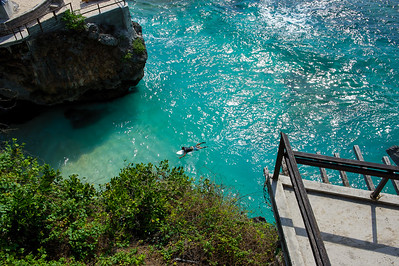 Surfer paddling in at Uluwatu, Bali Bukit, Indonesia