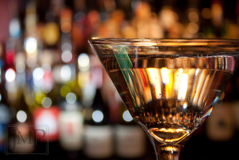 Bokeh at the Bar - A single glass in view before the shelves of bottles behind