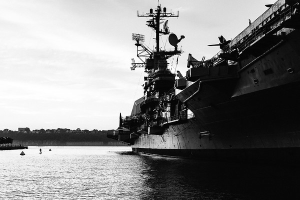 The silhouette of a man is faintly seen paddleboarding next to the USS Intrepid docked at Pier 86 in New York City