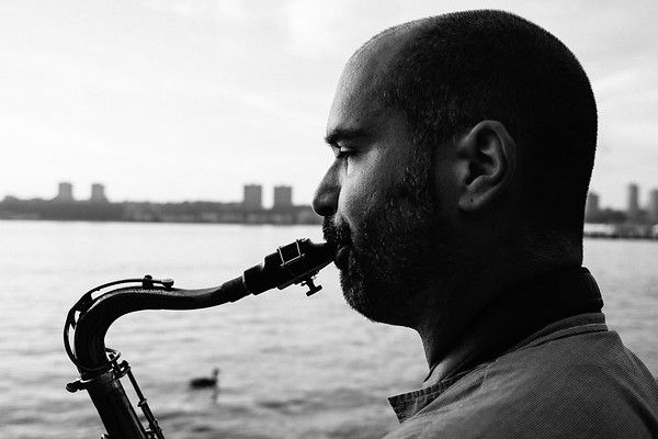 A man plays saxophone by the Hudson River