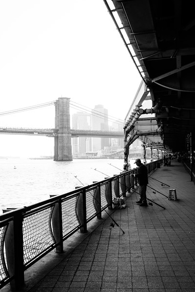A man tries his luck fishing with 4 poles under the FDR on the East River, Two Bridges, NYC