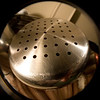 Close-up view of the bottom of a stainless steel steaming pot.