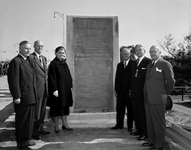 Governor Warren standing with Supreme Court Justice Mathews in group portrait by monument during the John E. Mathews Bridge dedication ceremony in 1953.
