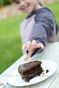 Comfort food.  Chocolate cake.  Child reaches to slice of cake