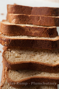 Homemade fresh crusty slices of bread arranged on a white chopping board