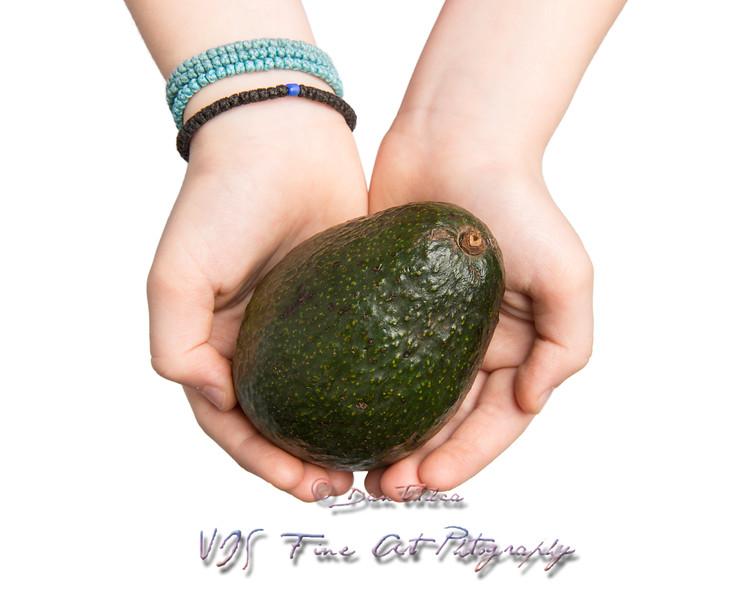 Hands Offering an Avocado