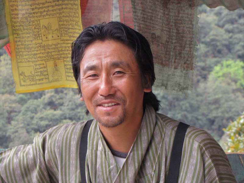 W-Norbu, local Bhutan guide with prayer flags in back