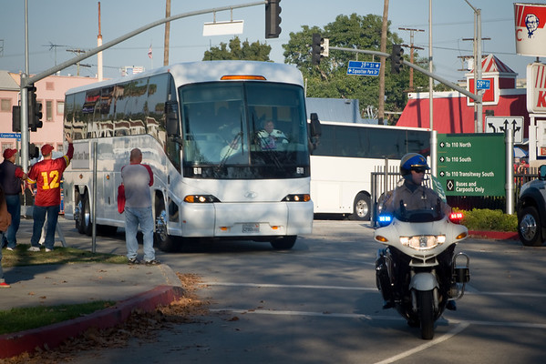 The USC football team arrives at the Coliseum via shuttle busses and with police escort
