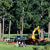Two foursomes around the 8th tee on a golf course, one is using a machine to dig their hole.