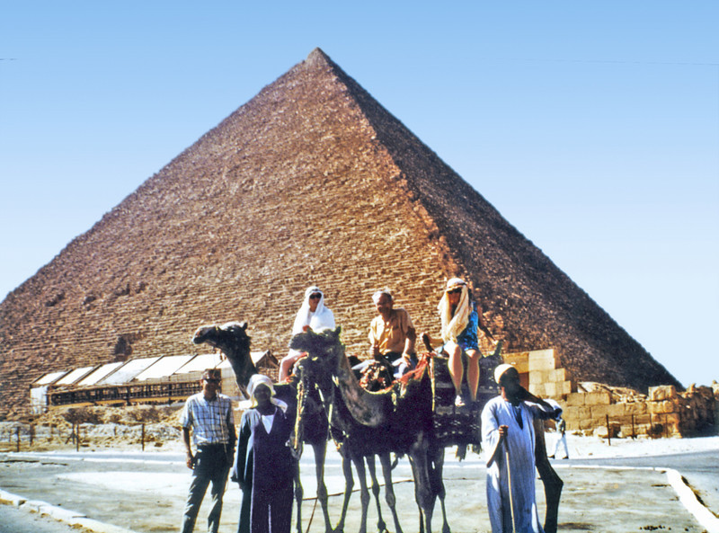 Egypt, Cairo (1971) - My family on camels below Cheops' pyramid at Giza. Low building in front of pyramid houses the famous funereal boat. From left: me, dragoman, mother, Dad, little sister Anni, and another dragoman.