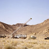 South Arabia (1964) - Erecting the mast of our truck-mounted Mayhew 2000 drilling rig. This rig drilled to 155% of nameplate capacity to reach basement at 3,006 feet at Hoowarin-1, the first of two wells we were to drill.