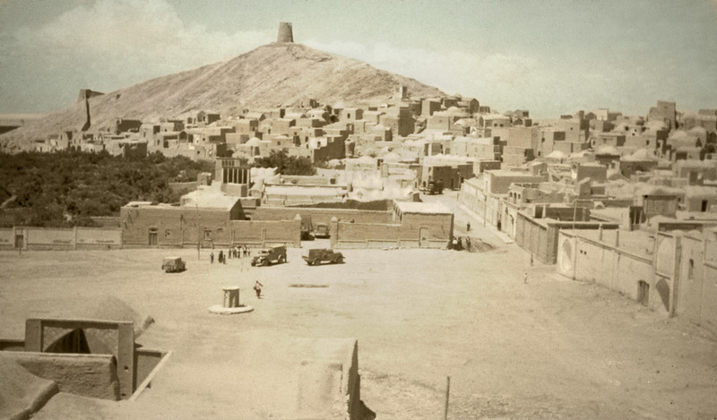 Iran, South Edge of the Dasht-i-Kavir (1959) - Little mining town of Anarak. When we first visited, the hilltop fortress was above the snow line, the town below it. The vehicles in the town square are ours. We were filling up at the town bowser.