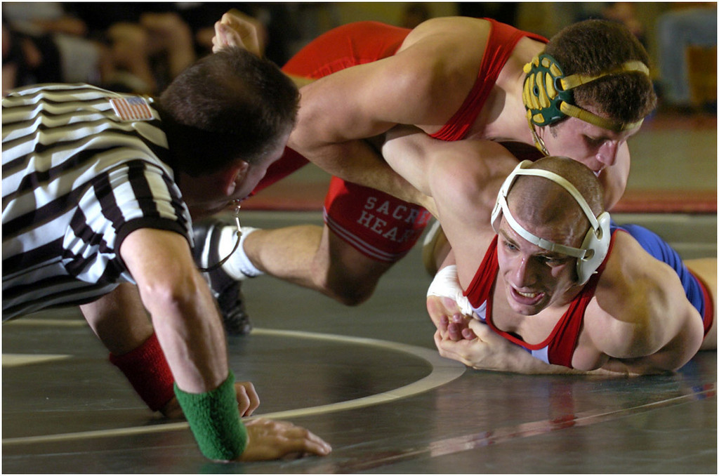 7.94x5.25deep---Ana Zangroniz photo for Palmer story to run Monday 12.6.04, Sports. Sherwood Fendryk of the Sacred Heart Academy (center) holds down Dwayne Hash-Barberis of American University in the 165-lb match. The wrestling duals were held at Niskayuna High School, on Sunday, December 5, 2004.