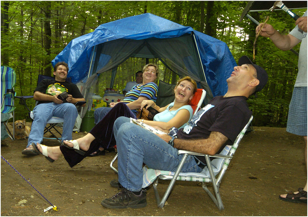 7.94x5.75deep---Ana Zangroniz photo for daily use, to run 7.6.04. Far right: Ilya Vatman (wearing hat) laughs as Lenny Levine pretends to nail a stick into his head. Vatman and Levine represented two out of ten families camping together at Moreau State Park. The ten families, all from the New York/New Jersey/Connecticut regions, have been camping together for the past twenty years. The come to Moreau State Park every year for the Fourth of July, and stay between a few days to two weeks.