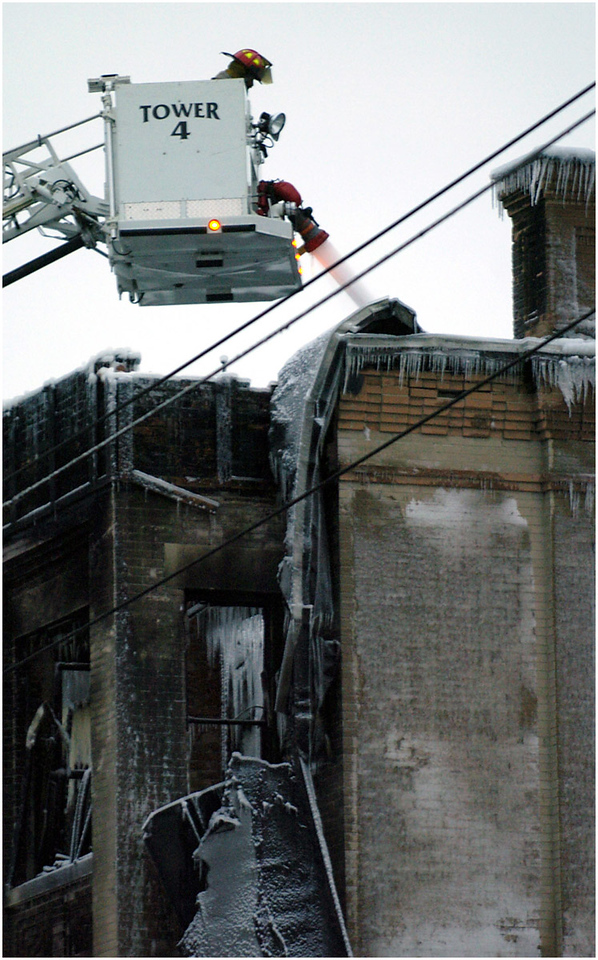 5.92x9.5deep---Ana Zangroniz photo for enterprise use, to run First Edition, Mon. 12.27.04. One day after the fire which gutted the building at 126 Division Street, a City of Amsterdam Firefighter continues to spray hot spots from a cherry picker extended over the four-story structure.