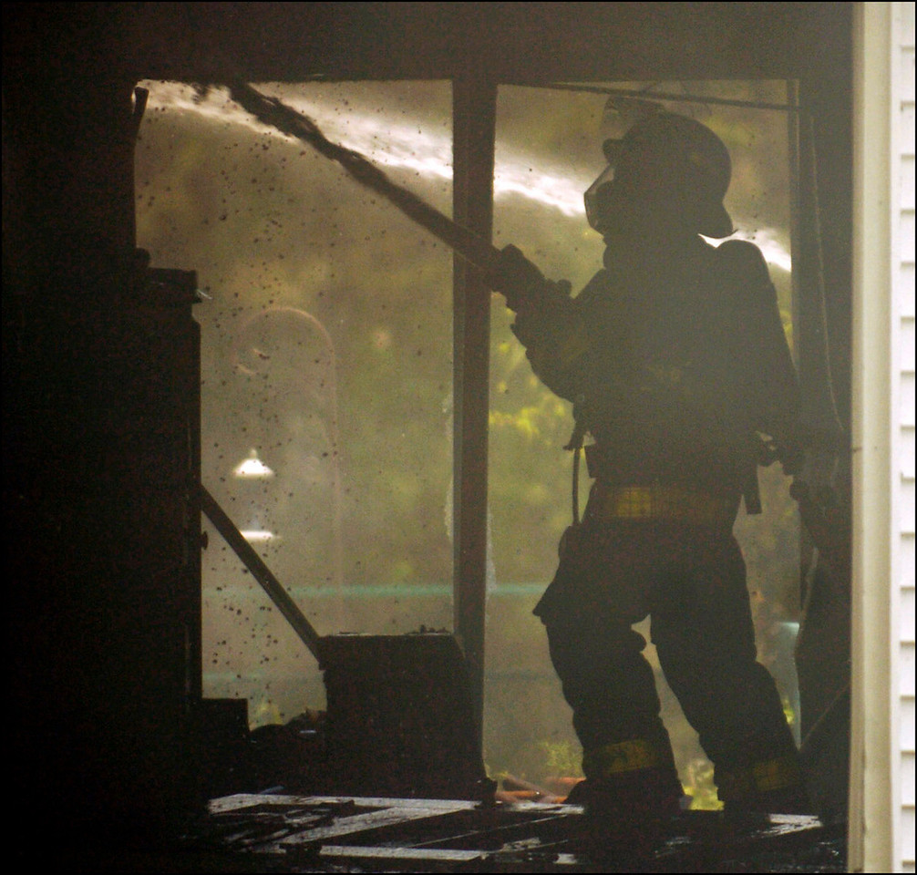 7.94x7.5deep---Ana Zangroniz photo for a Matt Volke story to run Saturday, May 21, 2005. Inside the garage of 21 Wing Road in Rexford, a firefighter works to extinguish flames that consumed the home on Friday, May 20, 2005. The cause of the fire has yet to be determined. *This photo is Ana's suggestion for dominant use between the two*