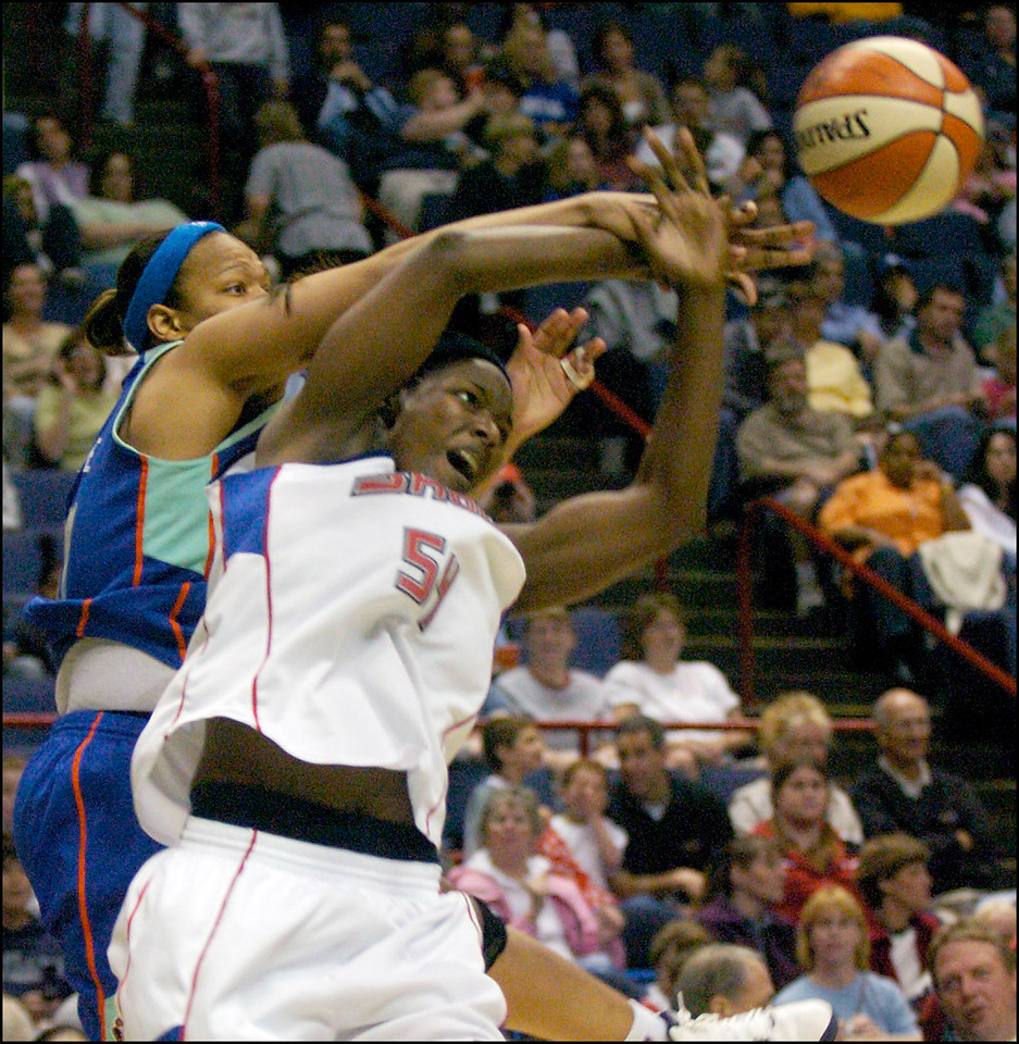 7.94x8.25deep---Ana Zangroniz photo for a Steve Amedio story to run Sports, Monday, May 16, 2005. Barbara Farris (54) of the Detroit Shock looses posession of the ball, knocked out of her hands by DeTrina White (left) of the New York Liberty.