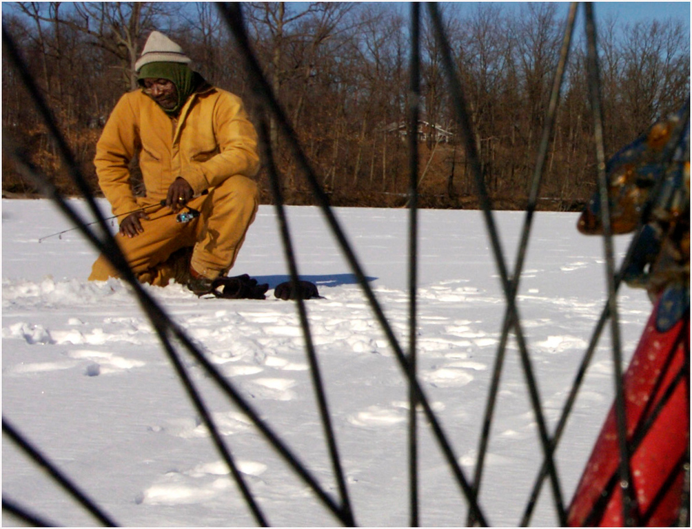 7.94x6.0deep---Ana Zangroniz enterprise photo for daily use, to run Monday Feb. 28, 2005. Glenn Frazier of Schenectady sits patiently on Collins Lake, hoping for some action as he ice fishes on Sunday, February 27, 2005. Frazier is seen through the spokes of the bike of 12-year-old Matt Wilsey of Scotia (not pictured), who came out onto the Lake to see how Frazier was faring.