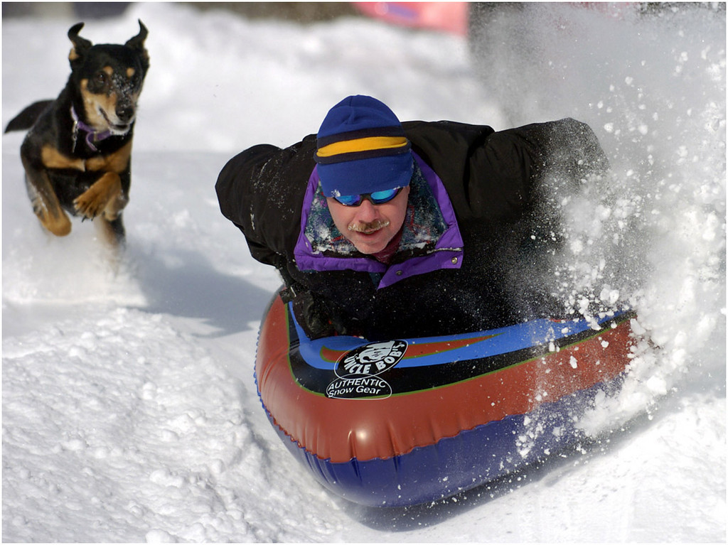 7.94x5.75deep---Ana Zangroniz photo for daily use, to run Monday Jan. 24, 2005. Sasha the dog chases after her owner, Mike Metcalfe of Schenectady, as he flies down a hill at the Schenectady Municipal Golf Course. Metcalfe and his children, along with their neighbors, came out to enjoy the beautiful warmer day on Sunday, January 23, 2005.