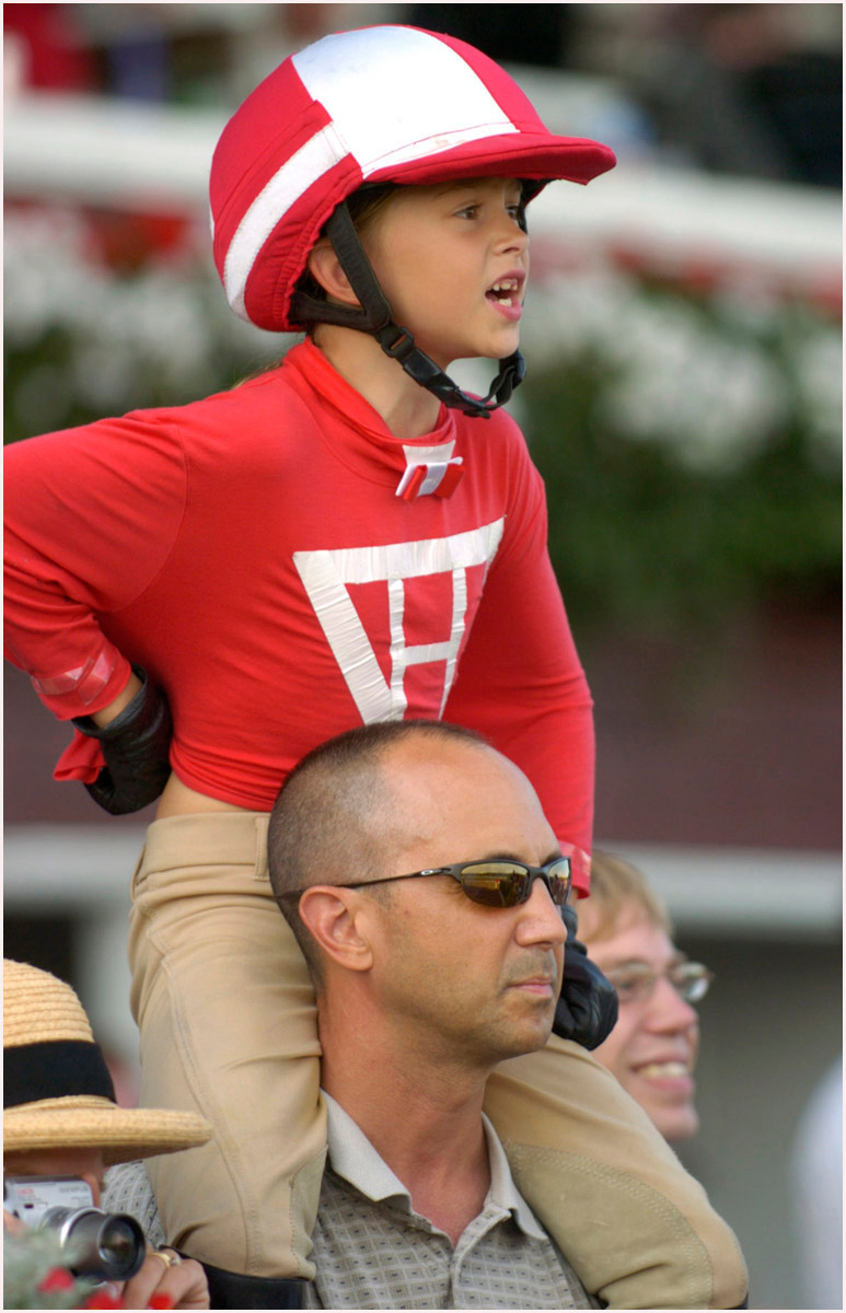 5.92x9.0deep---Ana Zangroniz enterprise photo for stand-alone use, to run Tuesday, August 16, 2005. Savanna Hajdasz, 8 (cq), of Hebron, CT, has a clear view from the shoulders of her father Stephen as she cheers for Shiree Armour during the final race of the day at Saratoga Race Course, Monday, August 15, 2005. Savanna proudly wore her Halloween costume from last year, the colors of Charles Howard that Red Pollard wore as Seabiscuit's jockey.