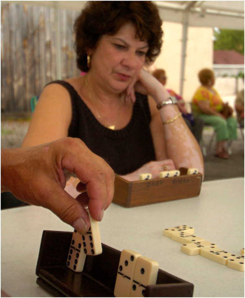 5.92x7.0deep---Ana Zangroniz photo for a Bob Conner story to run Sunday, August 21, 2005. Daisy Rivera, center, studies the dominoes on the table as Cecilo Soto, (hand), left, prepares to play a ficha (a dominoe chip). The two, along with Miriam Arocho and Felix Perez, competed in a dominoe tournament that was part of Centro Civico's Cultural Arts Festival, held on Main Street, Saturday, August 20, 2005.