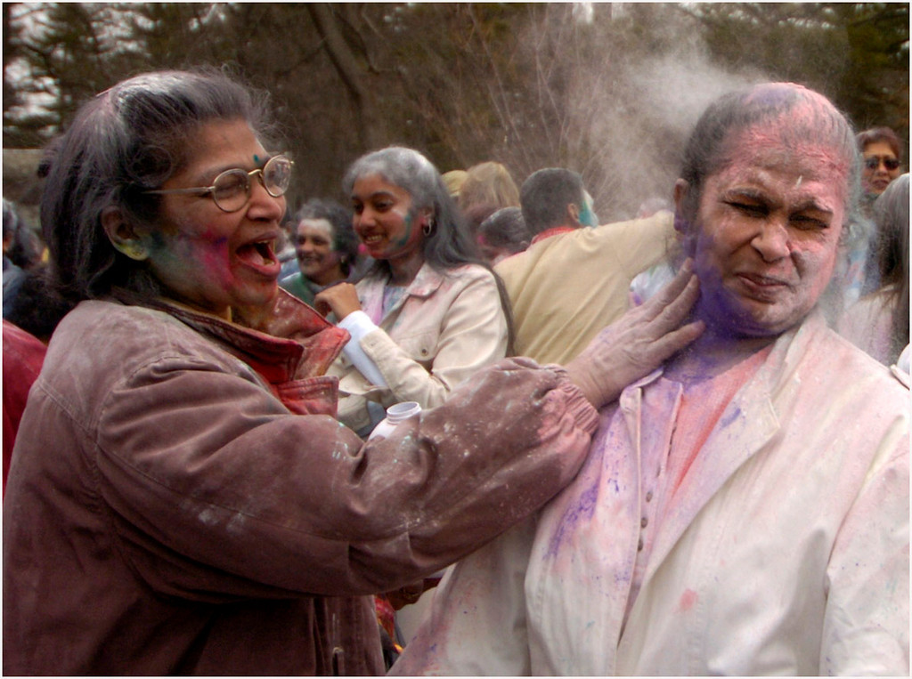 7.94X6.0deep---Ana Zangroniz photo for Dan DeVries story to run Monday, March 28, 2005. Usha Sharma (cq), right, closes her eyes as her sister Puhl Persab (cq), spreads purple powder on her face on Sunday, March 27, 2005. The various colors of powder represent the colors of spring. Perfume was also sprayed, representing the smells of spring.