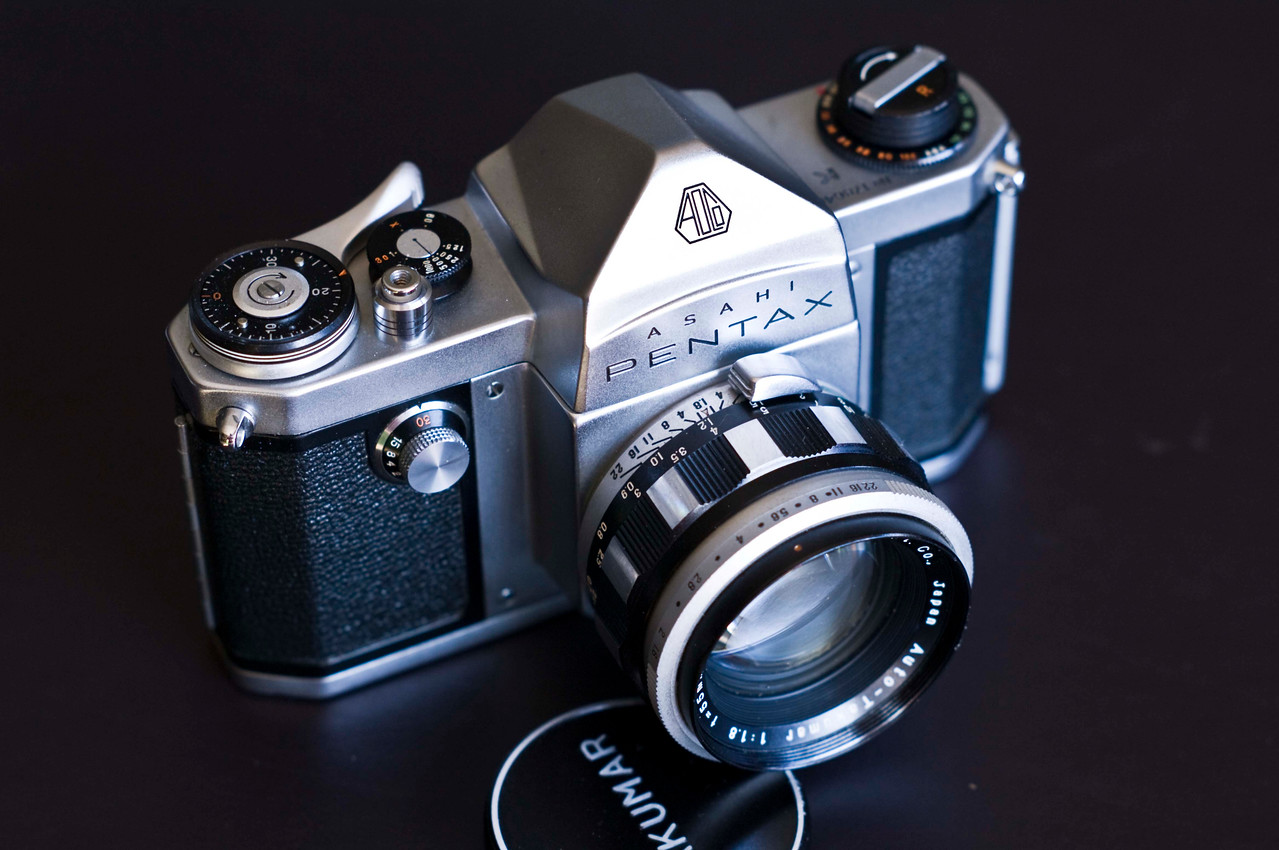 "In 1958 Pentax released the K or ""King"".  This was one of the first cameras with a (semi) auto-aperture feature.  A tab on the side of the lens is spring loaded.  Both the camera and the lens are cocked, then the shutter activates both the curtain and the blades inside the lens."