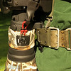 Detail how the Zuiko Digital 300/2.8 is hooked onto the combat harness belt via a custom lens replacement foot from 4th Generation Design. The red is a double loop of 2-mm Kevlar string for attaching the heavy duty snap hooks on an extra wide webbing Upstrap (designed for heavy bags).