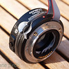 A <b>cleaved Zuiko Digital EX-25 extension tube with electrical bypass cable</b>. <p>What I essentially have done is cleaving the tube and putting in a set of OM-bayonets in the gap. The resulting tube is only 1 mm onger than the original but now it is possible to add extension tubes, a macro tele converter, bellows, etc between the camera body and any Zuiko Digital lens with maintained AF and aperture control from the camera body.