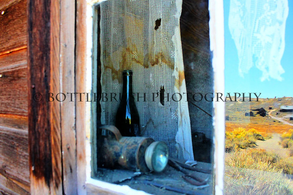 """Reflections""  Looking into a home in Bodie you can see everyday items left behind and the town in the reflection."