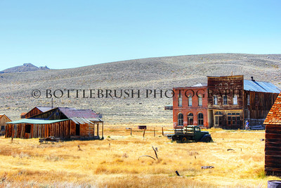 Two buildings on the far end of Main Street in Bodie, California.  Oddfellows Hall is the tall wooden one attached to the brick building.  You can make out I.O.O.F. on the front which stands for Independent Order of Odd Fellows.  Across from that is an old Ford V8 truck.