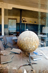 BI119  Interior of school room and old cracked globe.