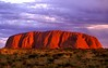 """05-06  Uluru Sunset ~ Australia.<br /> <br />     Located in Australia's Great Red Centre, this is not, as once believed, the world's largest monolith (Mt. Augustus in Western Australia is). It is one end of an extensive, mostly buried, very thick sandstone layer, bent by ancient tectonic actions to become nearly vertical. Over subsequent millions of years, erosion has revealed what is seen today.<br />  <br />     This rock is sacred to the Anangu, an aboriginal people whose culture goes back nearly 40,000 years. They named it Uluru, which I prefer to the English name, Ayers Rock. That name was bestowed by British explorer Wm. Gosses in 1873, to honor the Chief Secretary of Southern Australia, Sir Henry Ayers—a man who never ventured into the Australia's heart. <br /> <br />    Although the Anangu request that visitors respect their sacred rock by not climbing it, large numbers of tourists still swarm up the cable-protected route. Rather than climb, I chose to take a solitary (except for a billion or so tiny non-biting flies) pre-dawn hike around the Uluru's extensive base—in a clockwise direction, as one does around Buddhist stupas in the Himalaya. The sunrise was stunning! <br /> <br />    You may ask, """"Is that really the color?"""" Fair question. My 35-mm slide was made and processed in November 1997, digitally scanned only recently, worked on using Photoshop, and finally digitally printed. Thus, all the colors are the result of my best recollection, plus how colors were rendered by the various steps in the digital process leading to the final print. No attempt was made to intentionally exaggerate what was seen. I am very satisfied by the final print; it represents what I remember seeing. Uluru's sunset and sunrise colors are the result of three factors: 1) the oxidized sandstone is red; 2) the sandstone is filled with minute fragments of feldspar, each a tiny mirror; 3) the terrain is essentially unobstructed to both the eastern and western horizons. Light from th"""