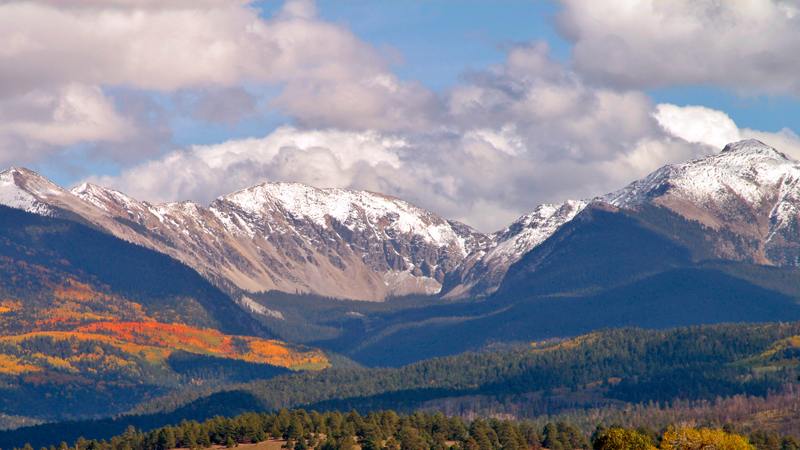 05-01 Truchas Peaks ~ September.<br /> <br /> At an elevation of about 13,100 ft., the Truchas Peaks—part of Northern New Mexico's Sangre de Cristo mountain range—are the fourth, fifth, and sixth highest points in the state. By mid-September, aspens on the peaks' upper slopes begin to change into their autumn colors. As the days pass, larger and larger areas become yellow, orange and gold. The high elevations usually receive the season's first snow, while below, the village of Truchas enjoys pleasant days and beautiful views.