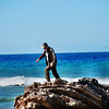 Preparing to jump off rock, timing the incoming waves